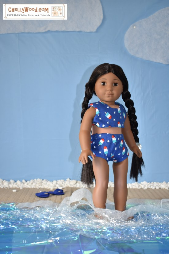 "The image shows an 18 inch doll (Kaya from the American Girl doll collection) wearing a handmade bikini. she stands with her feet in imaginary beach water (made from plastic table cloth, velum, and tinsel which makes the water look iridescent and foamy. Kaya's swimsuit is a bikini style, made of navy blue jersey fabric decorated in tiny stars and Popsicles. Behind her, sandals which were also handmade sit in the imaginary sand on a beach with a blue sky behind the beach.  The watermark says, ""ChellyWood.com"" and suggests that the free printable sewing pattern for making this bikini can be found at ChellyWood.com."