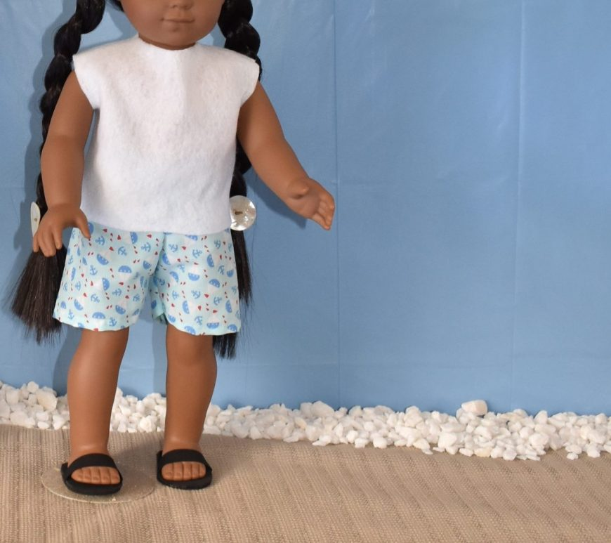 Here we see a Kaya doll in a beach diorama. she wears a white felt easy-to-sew top and a pair of elastic waist shorts made of nautical-themed blue cotton fabric. She also wears handmade black sandals.