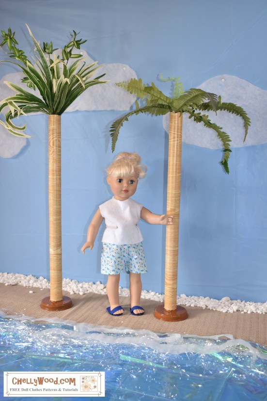 "The image shows an 18-inch (46 cm) Madame Alexander doll wearing handmade shorts and a sleeveless summer shirt. She stands on a sandy strip of beach with water in the foreground. On either side of her are pretend palm trees made of faux fern plans extending from a paper-covered cardboard tube that seems to ""grow"" out of the strip of sandy beach. The little doll looks happy in the sunshine of her home-made beach scene. The watermark says, ""ChellyWood.com: free patterns and tutorials."""