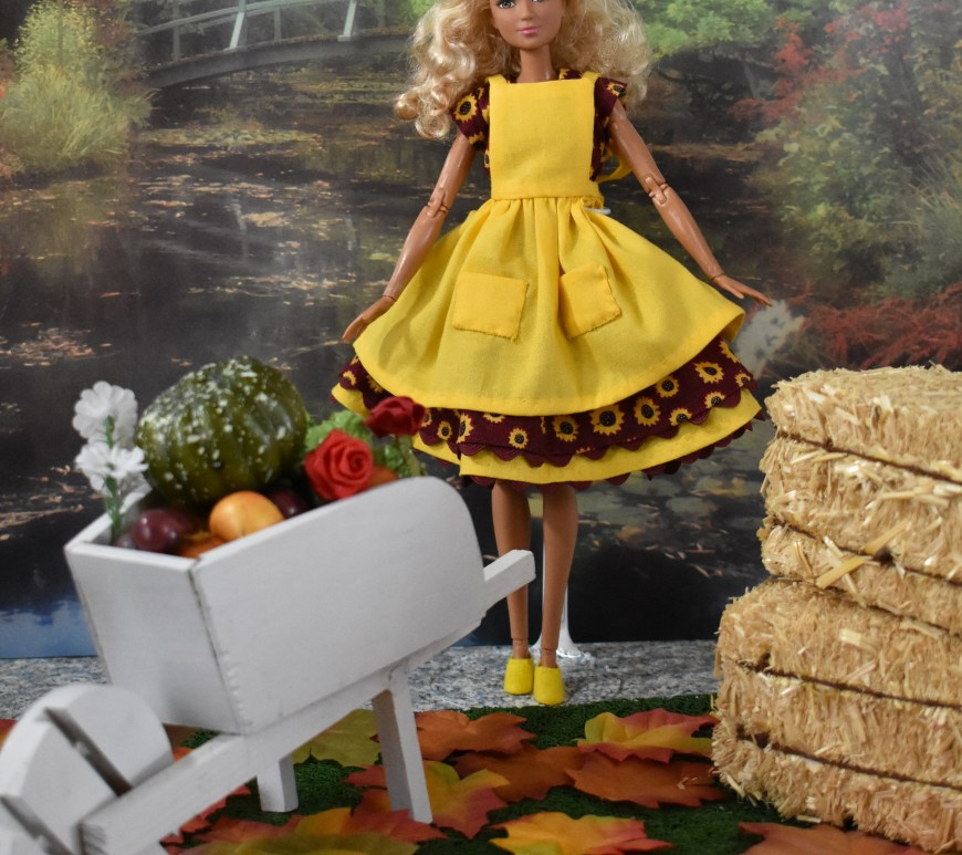 The image shows a Made to Move Barbie with blond hair and olive complexion standing in a fall setting. Before her is a tiny white wheelbarrow filled with harvest vegetables. At her side are bales of hay. She wears a pretty dress dotted with sunflowers on a burgundy fabric. The dress is trimmed with yellow rickrack. Over the top of this cap-sleeved dress is a sunflower-yellow apron with big pockets. She appears to be holding her skirt out to demonstrate its fullness. A smattering of fall leaves are at her feet. Behind her is a pond with trees that seem to be in various stages of changing from summer to fall foliage colors.
