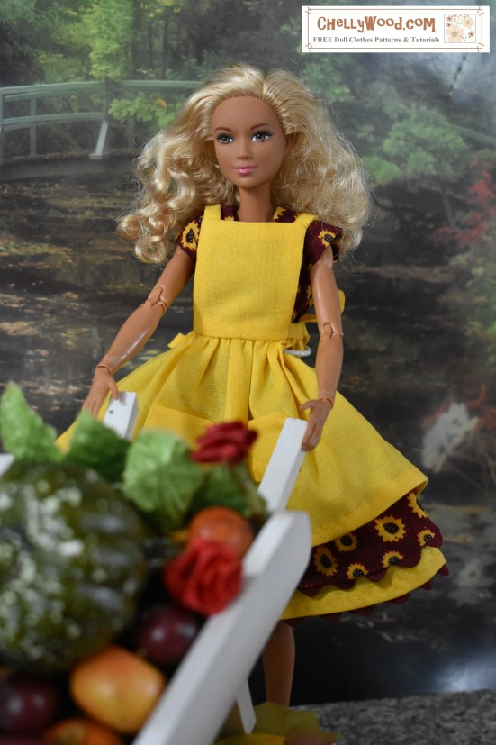 "Image shows a Made-to-Move Barbie wearing handmade clothes and holding the handles of a wheelbarrow in a fall harvest themed (i.e. Thanksgiving or Halloween theme) diorama. Behnd her is a garden surrounding a still lake. In front of her are the vegetables, leaves, and flowers from her garden, filling the basket area of her wooden wheelbarrow. She looks happy to have completed her harvest. The website URL on this image is ChellyWood.com and the watermark also says ""free sewing patterns and tutorials"" to indicate that this website offers instructions for making the handmade outfit this Made-to-Move Barbie is wearing, along with patterns and tutorials for dolls of many shapes and sizes."