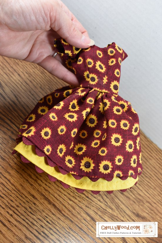 "The image shows Chelly Wood's hand holding a delicately hand-stitched dress made of burgundy fabric that's dotted with little yellow sunflowers. A yellow petticoat dips out from under the full skirt of the dress, and the dress's rickrack edging forms a wavy scallop along the division line between the dress itself and the petticoat. The dress has very short cap sleeves. The petticoat, too, has a scalloped edge, which has been formed by attaching rickrack to the underside of the petticoat. This handmade dress will fit Barbie and most 11.5 inch fashion dolls of similar size and shape. The overlay on this photograph says: ChellyWood.com, ""Free printable sewing patterns for dolls of many shapes and sizes."""