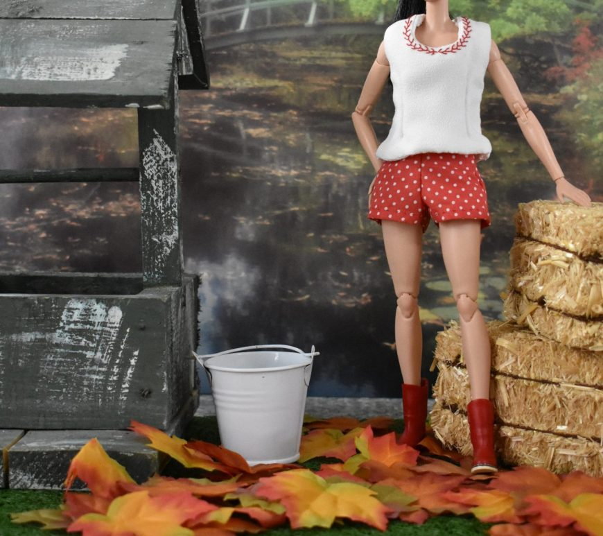 The image shows a Made-to-Move Barbie standing on a leaf-strewn lawn with a white bucket beside her. She leans against two bales of hay. She wears red rubber boots, a pair of red shorts with white polka dots, and a white sleeveless shirt that has been embroidered with tiny feather stitches around the neck. The neck's stitching is red to match her shorts and boots. She stands behind a wishing well. Would you like to make the outfit shown in this image? If so, please click on the link in the caption.