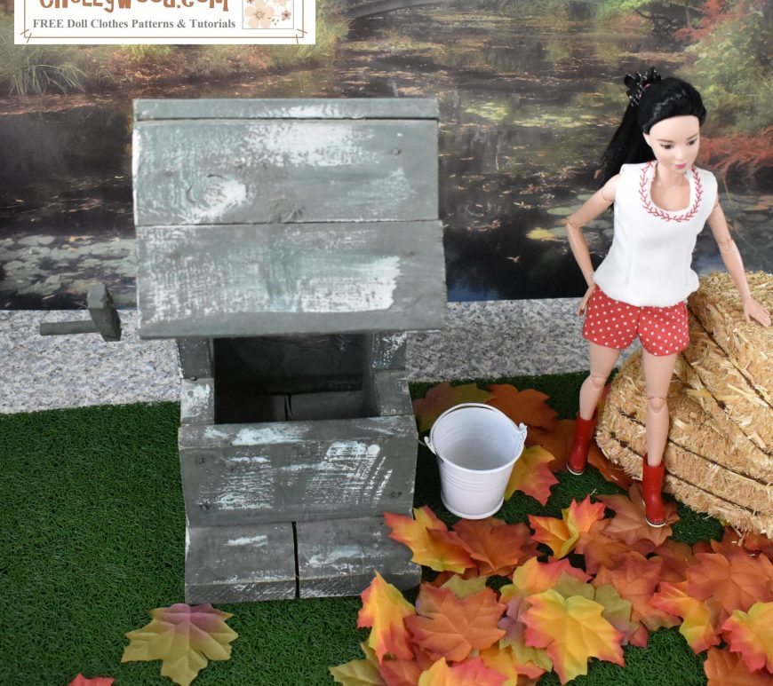 The image shows a Mattel Made-to-Move Barbie modeling handmade shorts and a white tank top. She stands in a decorative diorama with a fall harvest theme. There are autumn leaves of orange and yellow scattered around at her feet. There's a wishing well nearby and a white metal bucket. The 11.5 inch Mattel Barbie doll leans against a stack of baled hay. She wears a white tank top that has been delicately embroidered with a long row of feather stitches along the collar of the shirt. She also wears red shorts that have a tiny white polka dot pattern and a pair of red rubber boots. She appears to be out working in her garden, perhaps getting water from the well. Her black hair is done up in a pony tail. The doll is an Asian-looking Barbie doll, whose name is Miko, Kira, Dana, Becky,, or Nikki (depending on variations in the Barbie story line). The watermark on this image offers the URL ChellyWood.com, where you can find FREE printable sewing patterns to fit this Asian Made-to-Move Mattel Barbie and other similar-sized fashion dolls.