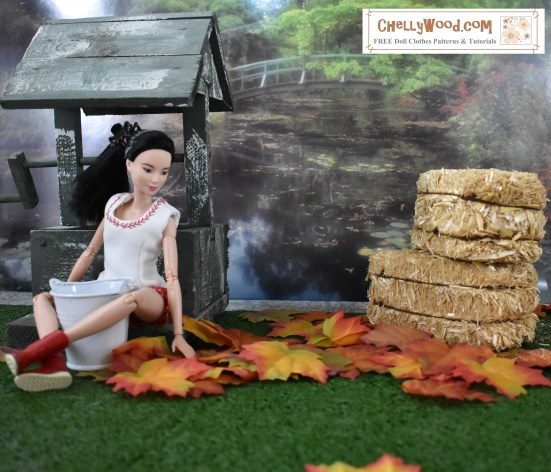 The photo shows Barbie sitting in green grass, surrounded by autumn leaves. There are two hay bales in the background of this tiny 1:6 scale diorama scene. Barbie leans her back against a wishing well, and in the distance behind her, there's a bridge in a garden. The bridge arches over a body of water like a lake, pond, or stream, with foliage all around. The watermark on this photo offers the website ChellyWood.com, which is where you can find hundreds of free printable sewing patterns for Barbie doll clothes, American Girl doll clothes, GI Joe, Ken dolls, Liv dolls, Polly Pocket, and dozens of other dolls of many shapes and sizes. All patterns on the website are free and printable, and each pattern comes with easy-to-follow instructions/directions in the form of a YouTube tutorial video.