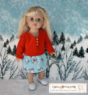 """This image shows an 18"""" doll wearing a red velvet shirt with tiny white buttons. It's a shirt with long sleeves. She also wears an elastic-waist skirt made of a cotton fabric that has a sky blue background and tiny snowmen patterns all over the fabric. The doll stands in a snow-scene diorama with pine trees and willow branches behind her on a snowy hillside. The sky in the diorama seems to be spotted with little snowflakes. The image has been watermarked with the URL ChellyWood.com (a website that offers hundreds of free printable sewing patterns for dolls of many shapes and all different sizes). If you download one of their free printable PDF sewing patterns for making these doll clothes, you are obligated to share images of the doll clothes and/or patterns with your friends, family, and followers, to fulfill the requirements of the """"Creative Commons Attribution"""" mark that's shown on each pattern. Once again, these doll clothes PDF patterns are free to the public, as long as you share the information about where you got these free doll clothes PDF patterns for 18 inch dolls."""