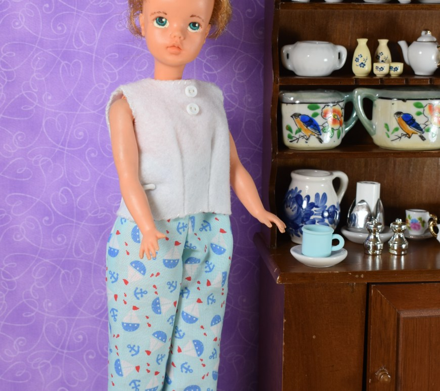 The image shows a Tammy doll (made by Ideal Toy Corporation) wearing a pair of handmade pants and a hand-sewn shirt. She stands next to a piece of furniture that is just her size, and it looks like a curio cabinet or china hutch. On this hutch are dozens of little tiny dishes with decorative paint, neatly arranged. The tammy doll's hair is drawn back in a pony tail. The wallpaper behind her is purple or lilac-colored. She looks at the camera with the forlorn eyes of the vintage Tammy doll, but it does look like she has been repainted with soft color to her lips. The fabric of her handmade pants is decorated with very small nautical print, showing sailboats, anchors, and very small red fish. The overlay explains where you can find the free printable sewing patterns for making this whole outfit: ChellyWood.com.