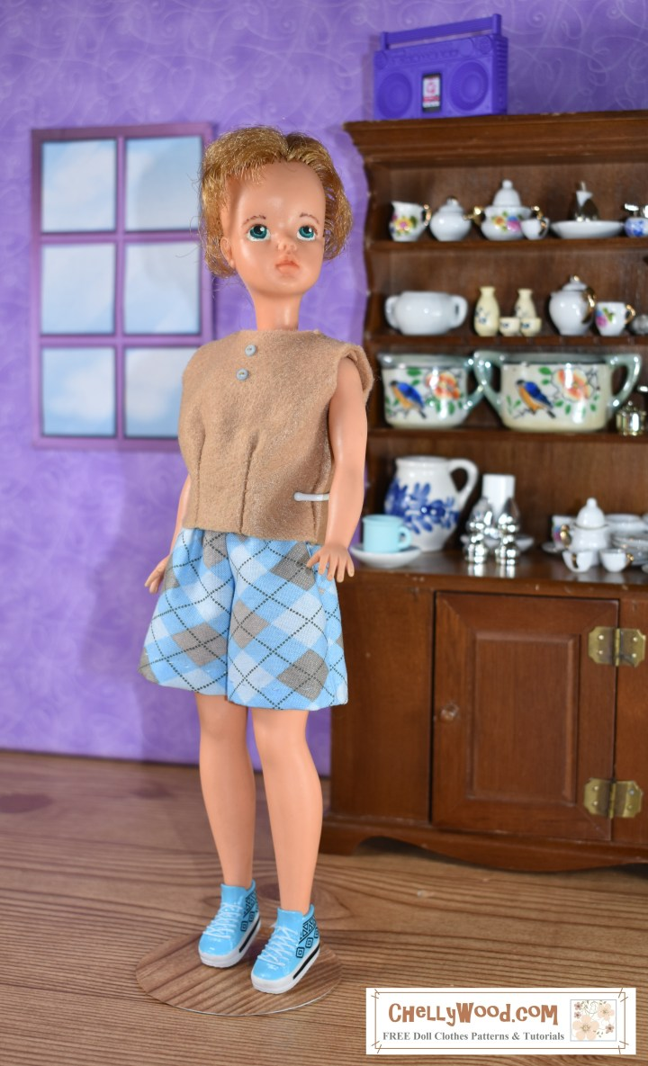 Find the free printable pdf pattern for this felt shirt to fit Ideal Toy Corporation's vintage Tammy dolls at ChellyWood.com. The image shows a Tammy doll modeling hand-sewn shorts and a hand-sewn sleeveless shirt made of felt. Tiny blue buttons adorn the front of this sew-easy shirt. The Tammy doll's shorts use a tiny argyle print, and she stands in a 1:6 scale room with a window and a hard wood floor. Behind her is a tall china hutch filled with itty bitty pieces of dishware. She models her handmade shirt with a fashion-model pose, her chin held high. The overlay offers the website where you can find more free patterns for doll clothes to fit Tammy dolls and other dolls of many shapes and sizes: ChellyWood.com.