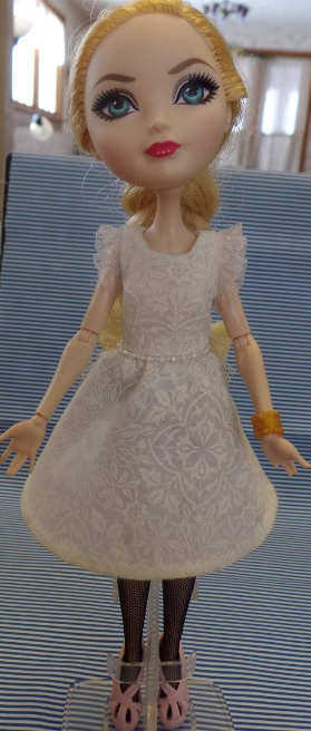 Image shows the full-front view of an Ever After High doll wearing a handmade off-white A-line dress with a beaded waist and lace-ruffle sleeves. the doll wears black hose and pink plastic shoes. The pattern used to make this dress is an alteration of a free pattern found at ChellyWood.com.