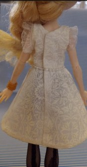 Image shows the back view of an Ever After High doll wearing a handmade off-white A-line dress with a beaded waist and lace-ruffle sleeves. This view suggests that the back closure on the dress is hidden. The pattern used to make this dress is an alteration of a free pattern found at ChellyWood.com.