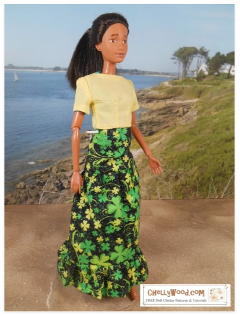 The image shows a Mattel Barbie doll wearing a handmade maxi skirt that is made of black glitter fabric decorated with gold and green shamrocks. The skirt itself is tiered with a ruffle at the bottom.