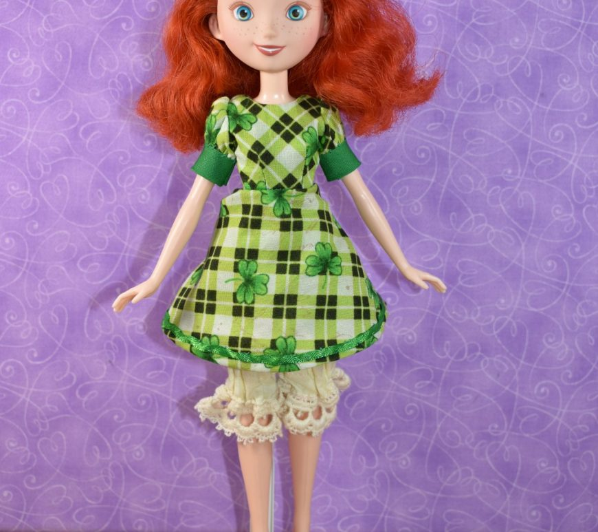 Merida wears a green plaid dress with short puffy sleeves that have green cuffs. The cotton dress is decorated with plaid black, green, and white colors overlaid with shamrocks. Under her dress, the doll wears handmade bloomers.