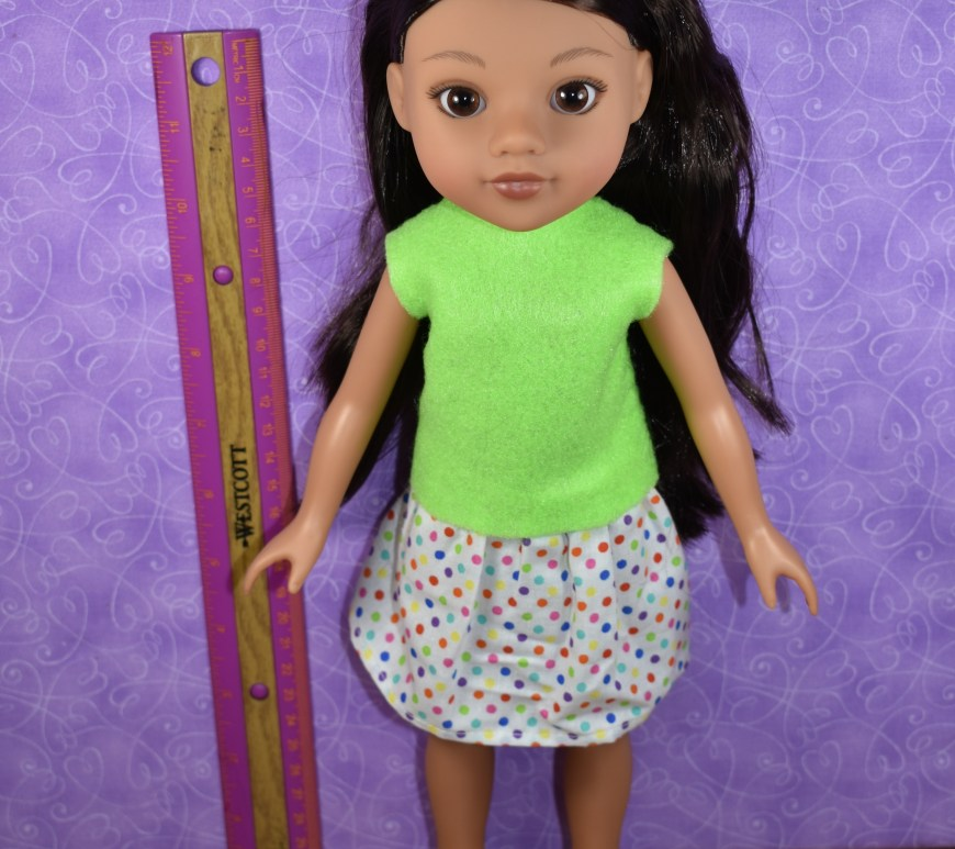 The image shows a Hearts for Hearts Girl wearing handmade doll clothes. She stands barefoot next to a ruler / measurement tool. The article associated with this image offers sewing measurements for the Hearts for Hearts Girls dolls.