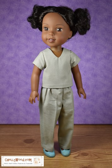 Click on the link in the caption, and it will take you to the page that has all the free printable PDF sewing patterns and tutorial videos you'll need to make this outfit. The image shows a Wellie Wisher Kendall doll wearing what looks like medical scrubs for 14 inch dolls. It's a V-neck shirt with a pair of elastic waist pants.