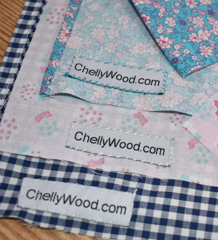 "This image shows three swatches of fabric which have a soft fabric sewing label sewn directly onto the fabric using a whipstitch. Each label says ""ChellyWood.com"" and the image goes with a blog post about where to buy craft labels like these."