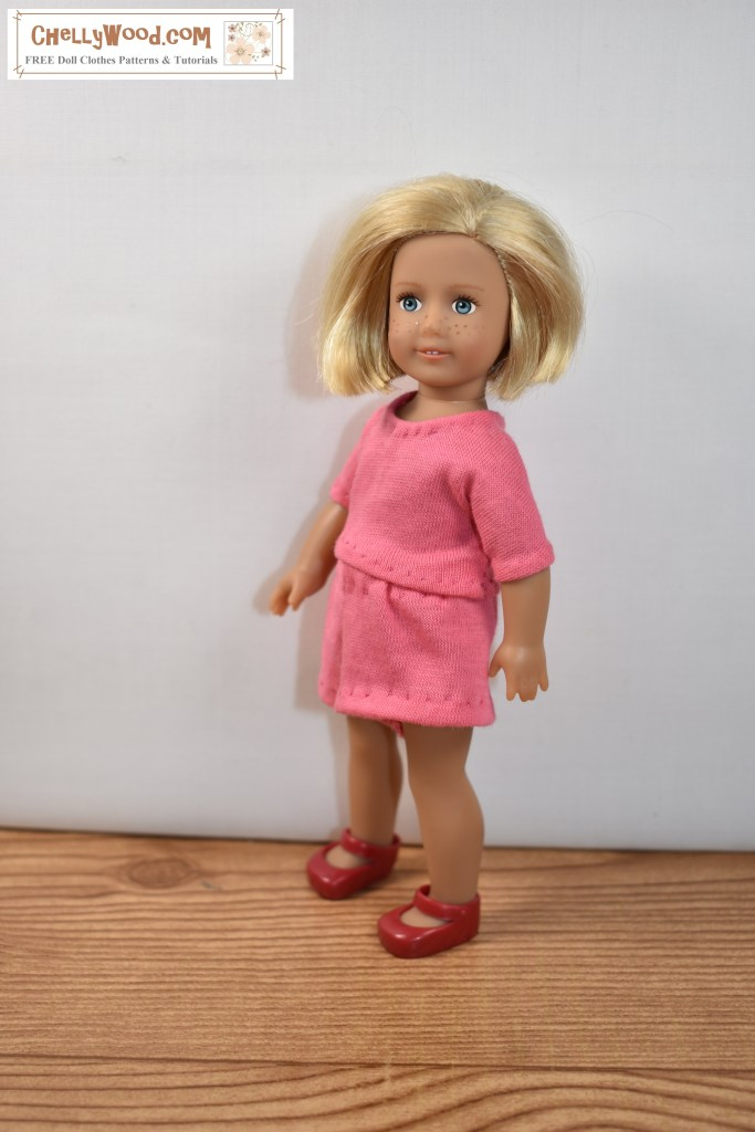 The image shows a little 6 inch American Girl doll (Kit Kittredge) wearing handmade doll clothes: a soft pink T-shirt and elastic-waist shorts. The website where this image is found is ChellyWood.com, and it offers free printable sewing patterns for both the T-shirt and the shorts, along with hundreds of other free printable sewing patterns (many are PDF format for easy download) for dolls of many shapes and sizes, including 6-inch dolls like the American Girl Kit Kittredge 6 inch mini doll.
