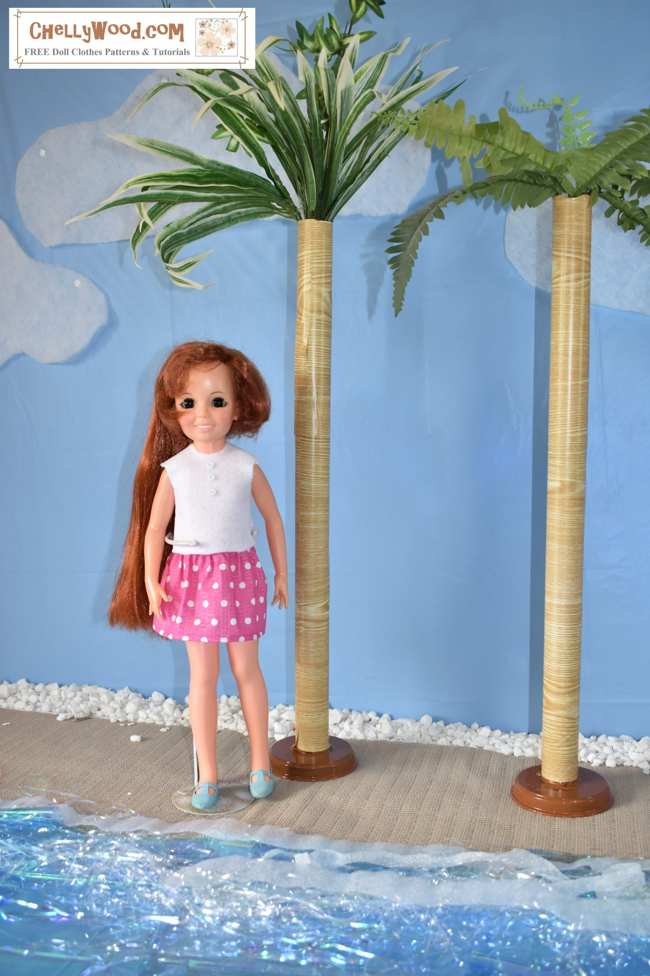A vintage Crissy doll stands beside two palm trees on a beach. She wears a very short mini skirt made of pink seersucker fabric with white polka dots. She also wears a white felt sleeveless summer shirt.