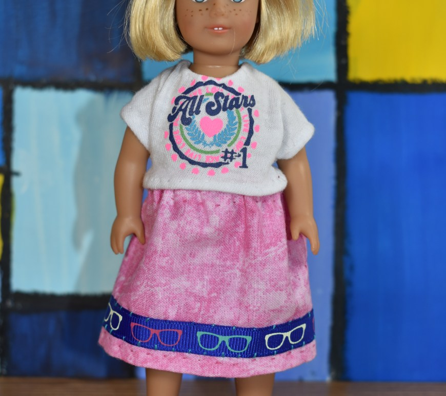 "The image shows a 6"" Mini American Girl doll wearing a handmade tee shirt and a handmade skirt. You can download the free printable PDF sewing pattern for making this outfit at ChellyWood.com."