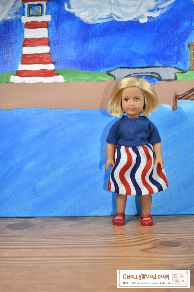 The image shows a 6 inch American Girl doll wearing a blue t-shirt with a wavy-striped cotton red-white-and-blue skirt. She stands before a seascape with a lighthouse in the background. If you'd like to make this outfit, please click on the link which will take you to the free printable PDF sewing patterns.