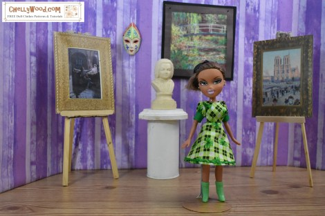 The image shows a Bratz doll wearing a hand-made A-line dress in St. Patrick's Day green plaid with shamrocks patterned on the cotton fabric. The dress has puff sleeves and cuffs. The doll stands elegantly amidst what appears to be a museum display of famous paintings, statuary, and clay art works. To download the free printable sewing pattern for making this doll dress and other doll clothes to fit Bratz dolls, please go to ChellyWood.com and click on the 8 to 9 inch doll clothes pattern category from the home page (20 cm to 23 cm dolls' clothes patterns). ChellyWood.com offers free printable sewing patterns and tutorial videos showing how to sew doll clothes to fit dolls of many shapes and all different sizes.