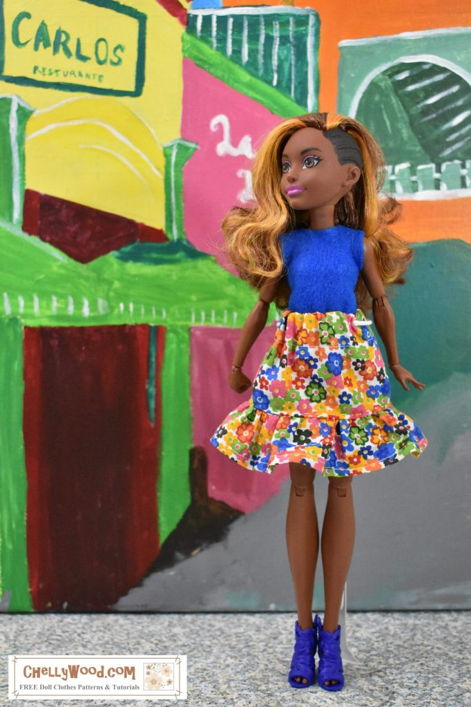 In a street corner in a Caribbean village, DC Superhero Bumblebee (the doll) wears a bright blue sleeveless felt shirt and a multicolored floral skirt with a ruffle. The skirt has an elastic waist and the tiny flowers dotting this cotton fabric include the rich royal blue of her shirt's fabric, plus hot pink, orange, yellow, and a smattering of green leaves.