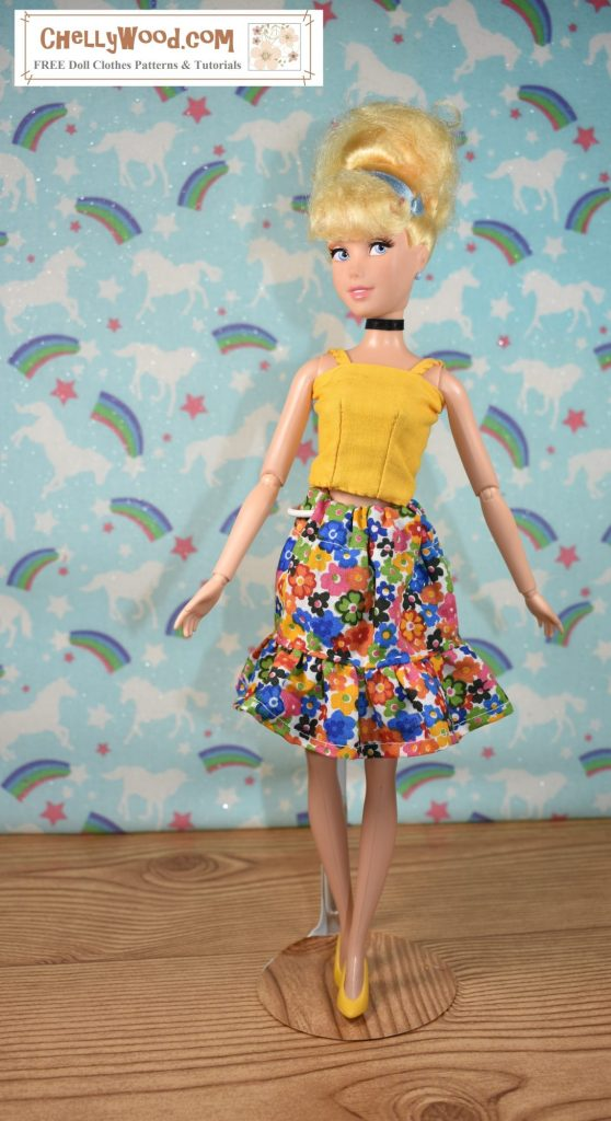 The photograph shows an older Disney Princess Cinderella doll who stands 11 and a half inches tall. She wears a handmade yellow strappy shirt with a multicolored elastic waist cotton skirt that has a ruffle.