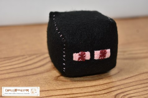"""The image shows Enderman from Minecraft. This is an easy-to-sew felt cube with a free printable PDF sewing pattern, which you can download at ChellyWood.com as a PDF file. The Enderman character is trademarked, so this is an """"unofficial"""" pattern, designed by patern designer Chelly Wood. You can make this felt Enderman character or other Minecraft characters into a foot sack, hackey sack (hacky sack) or plush toy using a simple free pattern and felt. Go to ChellyWood.com for this and other fun craft projects for boys and girls to make / sew with felt."""