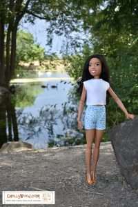 In this photograph, a 28 inch Best Fashion Friend Barbie stands beside a shimmering lake with clouds reflected in the water. In the distance are hills and greenery near the lake's distant shore. Over the Barbie's head are the leaves of a tall tree. The 28 inch Barbie doll wears a handmade one piece swimsuit of white spandex material. It fits her snugly with straps and an athletic style like an Olympic swimmer might wear. Not shown in this image, the swimsuit has a pretty keyhole opening in the back.