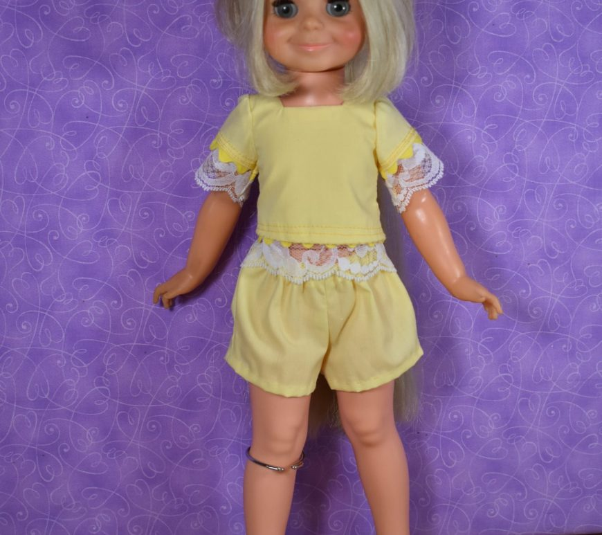 The image shows a vintage Velvet doll from the Crissy family of dolls modeling a handmade outfit of shorts and a lace-trimmed shirt.