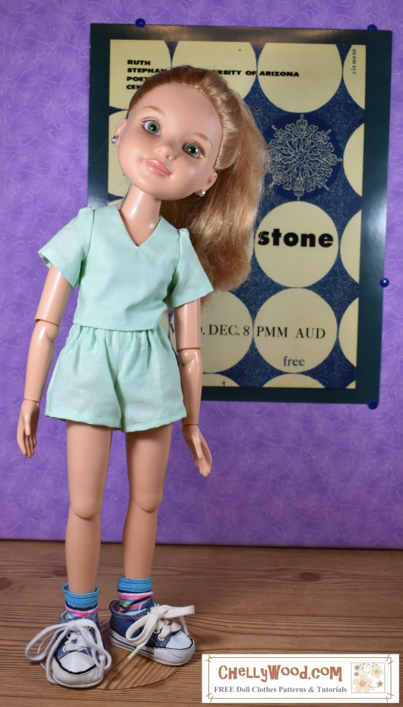 "Visit ChellyWood.com for free printable sewing patterns for dolls of many shapes and sizes. This photo shows a BFC Ink articulated 18 inch doll modeling a pair of handmade doll shorts with a pocket. She stands in front of a retro blue and off-white poster designed by the AU Poetry Center. The doll tosses her head to one side but appears to stand entirely on her own. The outfit she's wearing includes a V-neck shirt with short sleeves and a pair of shorts with a pocket at the back of the garment. You can download the free printable sewing patterns for making this outfit at ChellyWood.com (which is where you can also find a video tutorial showing how to make this outfit for 18"" dolls like the BFC Ink dolls). It should be noted that this pattern will not fit American Girl dolls."