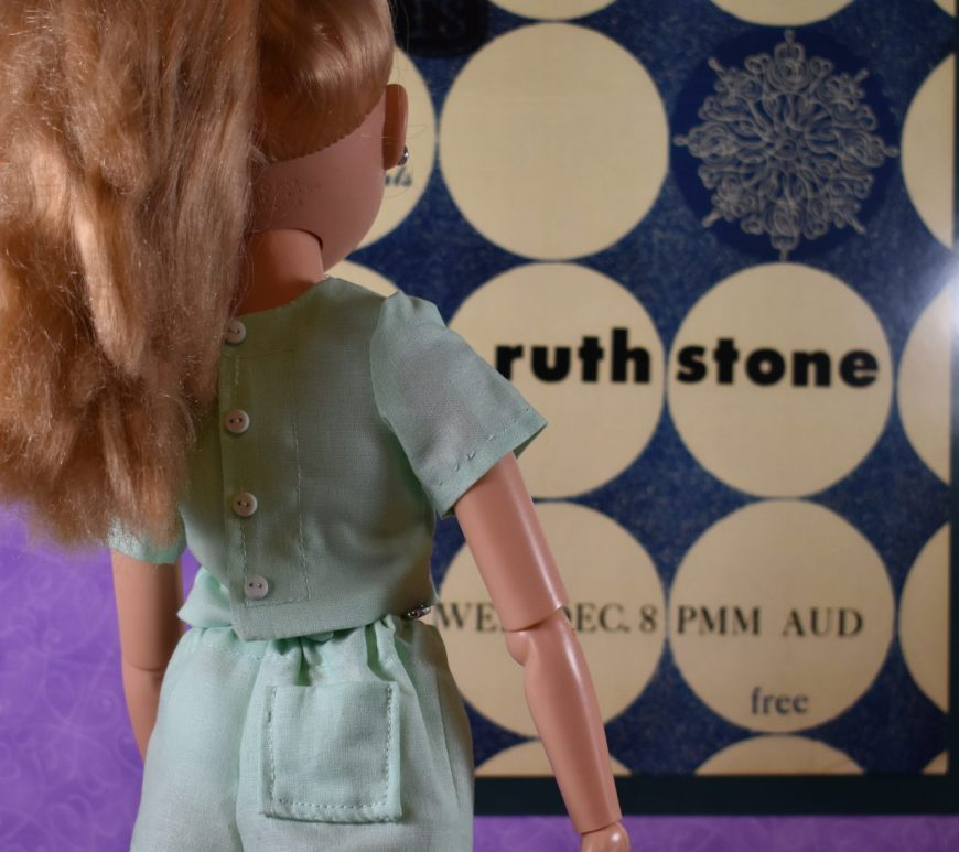 """This photograph of a Best Friends Club Ink doll appears to be taken indoors at an art museum. The doll stands before a modern art poster with the name """"Ruth Stone"""" inside identical side-by-side cream-colored circles on a blue background. The doll's back is to us, so we can clearly see that her elastic shorts have one working back pocket, and her close-in-back shirt has several tiny buttons running down the back closure area of the short-sleeved shirt. The shorts outfit she models is made of mint green cotton fabric."""