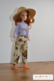 """Click in the link provided in the caption to navigate to the page where all the free patterns and tutorials are located for making this outfit. The image shows """"Flower"""" (a doll from the World of Love collection) wearing handmade doll clothes including a pair of ankle pants and a long-sleeve shirt. The free printable sewing patterns for these doll clothes are found at chellywood.com"""