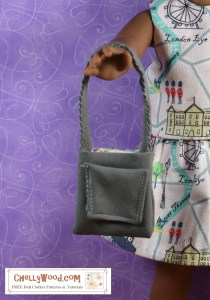 "The image shows a partial photo of a doll in the 13-inch, 14-inch, 15-inch, 16-inch, 17-inch, or possibly 18-inch doll range holding a handmade purse with a pocket. The watermark says ""ChellyWood.com: free doll clothes patterns and tutorials."" If you click on the link below the photo, it will take you to a page where you'll find a tutorial video and free printable PDF pattern for making a purse like this one with a side pocket and lining, to fit dolls in this size range."