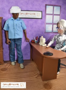 The image shows a GI Joe action figure wearing a pair of denim jeans and a blue cotton shirt. The shirt has tiny buttons down the front and a little pocket on just one side. The shirt has rolled sleeves and a collar. He wears a felt hat that may pass as a sailor's cap. He stands next to the Chelly Wood doll's sewing desk. Chelly sits at the desk and the dolls / action figures appear to be talking to one another about an upcoming sewing project (or other business type of transaction). You're welcome to pin this image on Pinterest or share it on social media, but please tell people that this image comes from ChellyWood.com