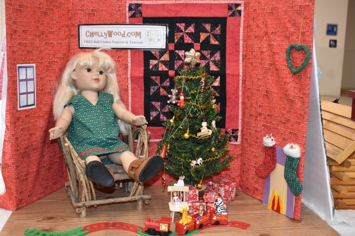 "The image shows an 18"" Madame Alexander doll seated near a tiny quilt and a little doll-sized Christmas tree. In front of her is a choo-choo train for dolls, a fireplace framed with stockings, and a heart-shaped wreath; behind her is a sign that advertises the website ChellyWood.com, where you can download free, printable sewing patterns for dolls of many shapes and sizes."