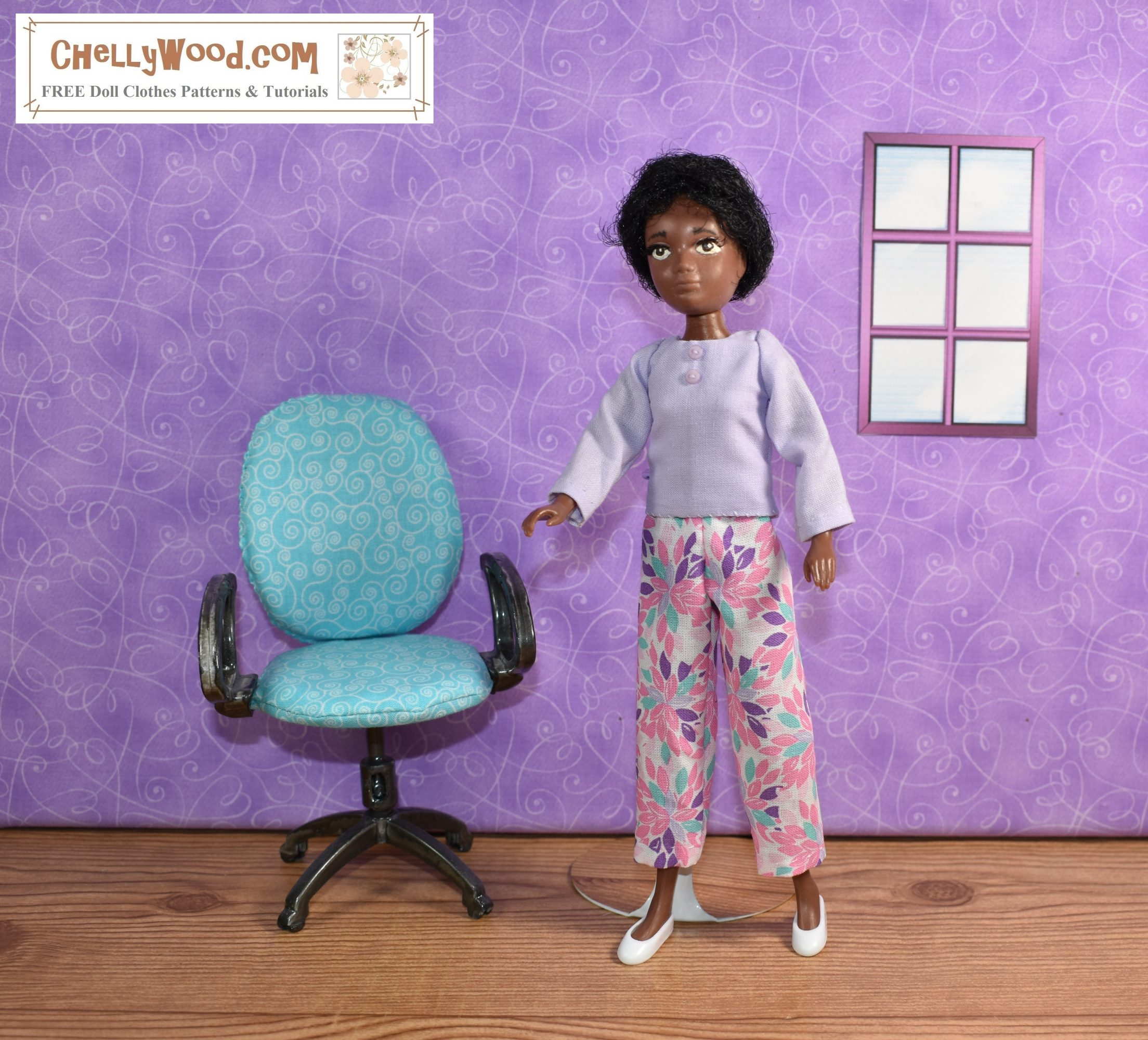 A World of Love Soul doll stands next to an office chair that has turquoise blue upholstery. Behind her, in the wall, is a tiny window on a purple-painted wall. The doll wears handmade floral ankle pants and a lavender long sleeved shirt with faux buttons down the front of the shirt. Her white plastic shoes sharply contrast the brown of the wooden floor.