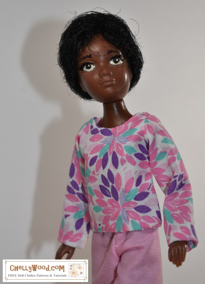 "The image shows one of the collectible vintage World of Love dolls (Hasbro) wearing handmade doll clothes. The long-sleeved shirt has a pink and purple leafy pattern on the cotton fabric. The pants the doll wears are made of pink cotton. Visit ChellyWood.com for free patterns to sew these doll clothes for your World of Love dolls or other 9"" dolls."