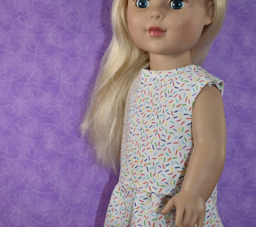 "In this image, we see an 18 inch doll modeling a sleeveless shirt with an elastic-waist skirt. The fabric is made of a confetti-patterned cotton. The patterns are free and printable for sewing these doll clothes for your 18 inch dolls, using the ""Creative Commons Attribution"" mark, and you can download the free PDF patterns for these doll clothes at ChellyWood.com (but by downloading these free PDFs you agree to share images of these patterns with your friends, family, and followers, so they too will know where to find free printable sewing PDF patterns for 18"" doll clothes online)."