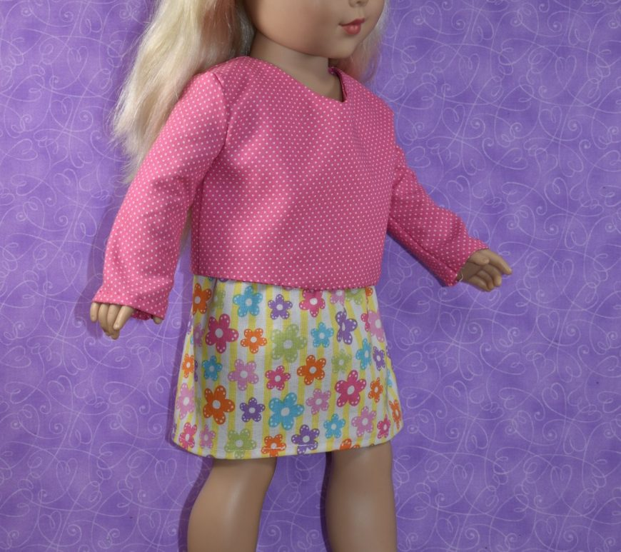 """This photo shows a cute little blond-haired 18 inch doll who appears to be walking, taking steps in her Sunday best. She wears a pink long-sleeve cotton shirt with a slight V-neck and teeny-tiny white polka dots and a yellow skirt that has little pastel-colored flowers that seem to also be spotted with polka dots. At the bottom of the image, near her high-stepping MaryJane shoes, there's a watermark: ChellyWood.com . On this website, you'll find hundreds of free printable PDF sewing patterns for making doll clothes to fit dolls of many shapes and all different sizes. Each pattern has been watermarked with the URL ChellyWood.com and the """"Creative Commons Attribution"""" mark, which means that by downloading these free doll clothes patterns, you agree to share images of the patterns with your family, friends, and followers, letting people know where you got the patterns."""