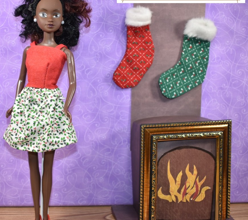 This image is a preview of what Chelly Wood has in store, as far as free patterns and tutorial videos for the week of 9 December 2019 through 13 December 2019. The image shows a Queens of Africa Azeeza doll modeling a handmade felt strappy summer top and an above-the-knee length skirt made of holly-patterned fabric. On the chimney behind her, above the fireplace in her 1:6 scale diorama, there are handmade stockings hanging by the hearth. Visit ChellyWood.com to find out how to make these projects, including the diorama of the fireplace with hearth, the stockings, and the handmade doll clothes for 11 inch fashion dolls. Visit https://queensofafricadolls.com/ to find out how you can purchase one of these lovely African heritage dolls.
