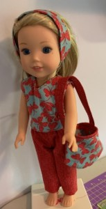 Image shows a Wellie Wisher doll wearing handmade pants in red fabric with a purse, sleeveless shirt, and headband made of grey-blue fabric with a red butterfly print. Patterns were designed and posted on ChellyWood.com as free printable sewing patterns to be downloaded by the public. Sewing was done by blog follower Dorothy (Dottie) L.