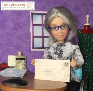 "The image shows the Chelly Wood doll holding an envelope. Beside her is a sewing machine and behind her is a dess form modeling a handmade doll dress. The watermark says, ""Chelly Wood dot com : free patterns and tutorials."""