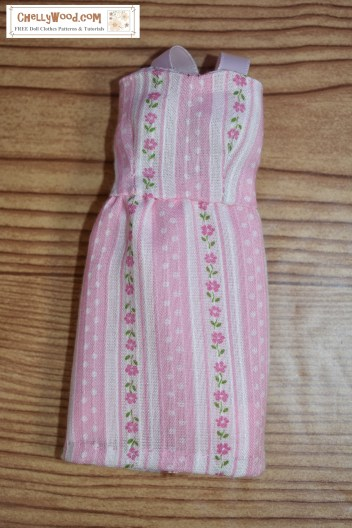 "This image shows a pretty handmade dress made of thin pink material decorated with polka dots and flowers on pink and white striped fabric. The dress has a short, straight skirt and a summery bodice with straps made of ribbon. The watermark says, ""ChellyWood.com: Free doll clothes patterns and tutorials."""