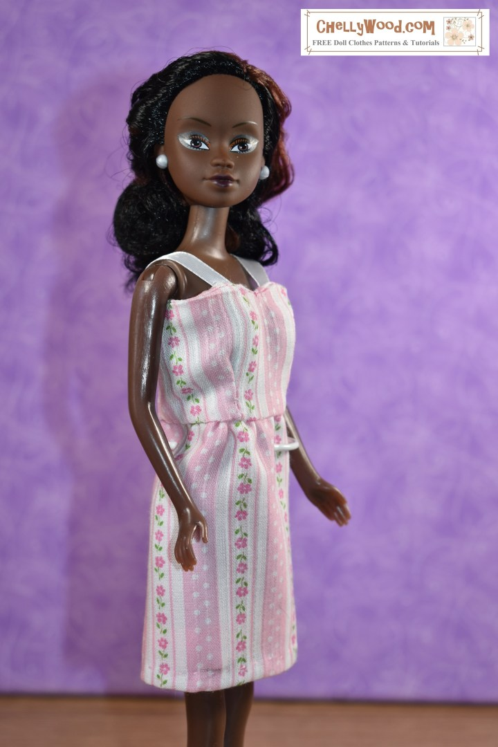 """This image shows a Queens of Africa doll wearing a pretty handmade dress made of thin pink material decorated with polka dots and flowers on pink and white striped fabric. The dress has a short, straight skirt and a summery bodice with straps made of ribbon. The watermark says, """"ChellyWood.com: Free doll clothes patterns and tutorials."""" The Queens of Africa dolls have a body shape similar to a Barbie-sized doll. She stands 11 inches high and has dark chocolate complexion. Her hair is quite curly. To purchase a Queens of Africa doll, go to https://queensofafricadolls.com/ In this particular image, the doll seems to stand tall, like she's proud of her African heritage. Her chocolate complexion contrasts the pink and white stripes in a lovely way."""