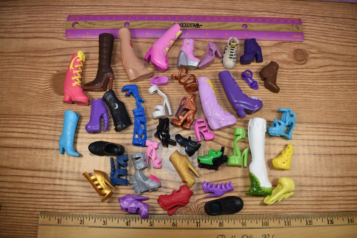 The image shows single (no-mate) shoes and boots in sizes that fit Barbie, Equestria Girls, Monster High, Ever After High, and Ken dolls. These items are SINGLE shoes with no mates. They are for sale at the following URL: https://www.ebay.com/itm/274314906705 and Chelly Wood is selling these single shoes to help her clear the storage areas in her closet, so she can make room for new dolls and additional sewing supplies. She's also trying to raise a little money to purchase an upgrade for her free doll clothes sewing pattern website, ChellyWood.com