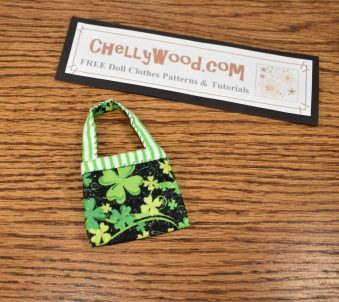 """The image shows a pretty fashion doll purse in green, white, black, and yellow. The strap of the doll's purse has green and white stripes. The body of the purse is made of black fabric decorated with green and yellow shamrocks. It's just the right size for 11"""" to 12"""" fashion dolls like BarbieDolls, Liv Dolls, Poppy Parkers, Skippers, Francies, Midges, and similar-sized dolls. There's a sign above the purse that says where you can find and download the free printable PDF sewing pattern for this dolls' purse: ChellyWood.com"""