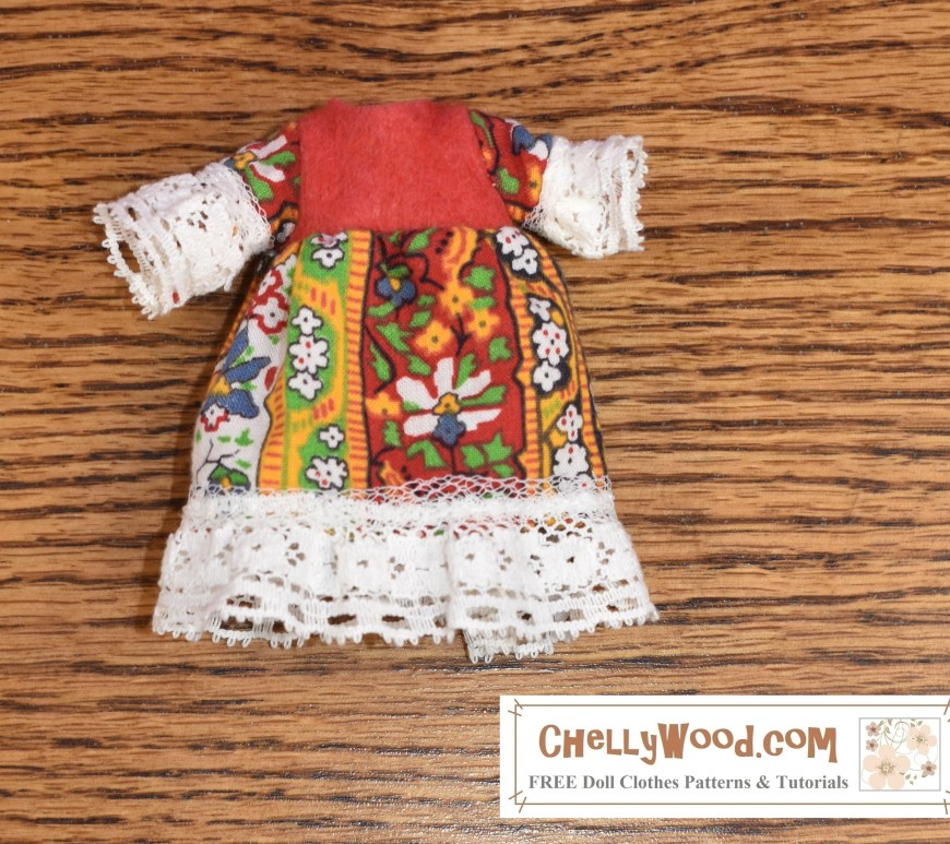 This image shows a tiny folk dress that has a felt bodice with a decorative cotton skirt and sleeves. The skirt and sleeves are embellished with lace trim. The free printable sewing pattern for making this tiny dress (to fit dolls that stand 4 inches, 5 inches, or 6 inches tall) can be found at ChellyWood.com under the correct size for the doll.