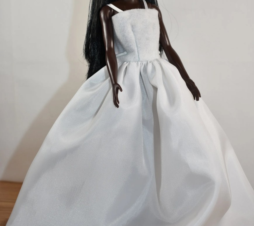 The image shows a modern Barbie doll wearing a wedding dress with an easy-to-sew felt bodice that has straps and a silky-looking long skirt. Click on the link in the caption, and it will take you to a page where you can download and print all the free printable sewing patterns for making these doll clothes, along with links to tutorial videos that show you how to make this outfit.