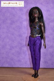 The image shows a modern Barbie doll wearing handmade ankle pants with a handmade tank top. The tank top is reversible. Click on the link in the caption, and it will take you to a page where you can download and print all the free printable sewing patterns for making these doll clothes, along with links to tutorial videos that show you how to make this outfit.