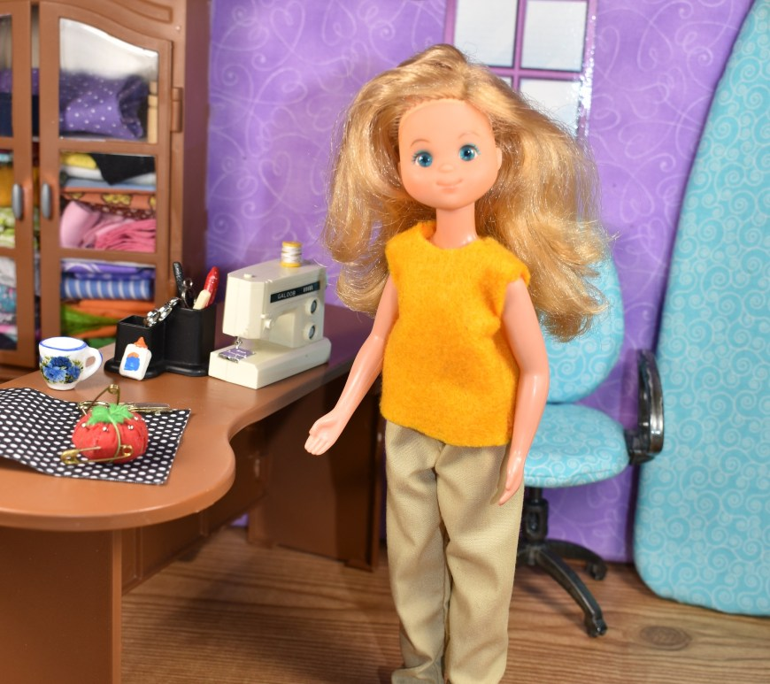 The image shows a tiny 1:6 scale sewing room with miniature sewing machine, coffee cup, fabric, ironing board, desk, glue, scissors, and a miniature tomato-shaped pincushion. Standing before the sewing desk is a Vintage Sunshine Family Mom or Mother doll from the 1970's. She wears a yellow felt sleeveless shirt that looks really easy to sew! And a pair of elastic-waist tan pants. Her plastic yellow shoes are loafers in a 1970's style. The watermark tells you where you can download and print free PDF sewing patterns for making doll clothes to fit this Sunshine Family doll: ChellyWood.com
